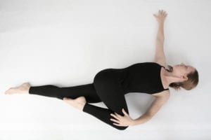 lady twisting her torso to relieve hip pain caused by work injury