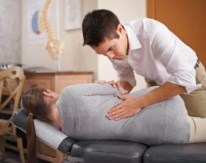 chiropractor manually adjusting woman's back for low back pain