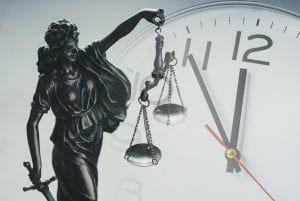 Statute of Limitations Clock behind Scales of Justice